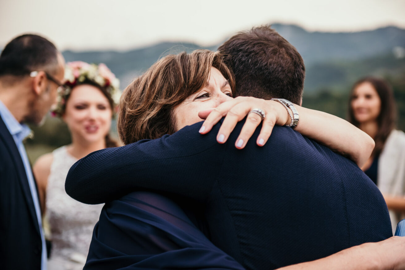 Matrimonio a Bologna sui colli, abbraccio invitati e sposo a Marzabotto all'agriturismo Aldilà del Fiume